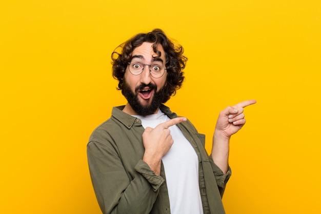 Młody szalony człowiek czuje się radosny i zaskoczony, uśmiecha się ze zszokowanym wyrazem twarzy i wskazuje na boczną żółtą ścianę