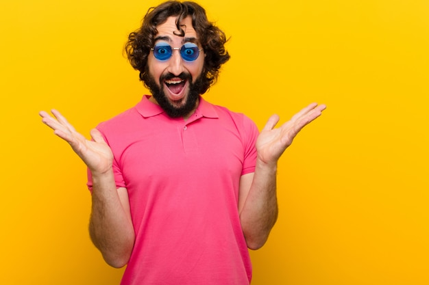 Młody szalony człowiek czuje się szczęśliwy, podekscytowany, zaskoczony lub zszokowany, uśmiechnięty i zaskoczony czymś niewiarygodnym na tle pomarańczowej ściany