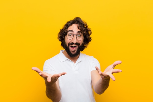 Młody szalony człowiek czuje się szczęśliwy, zdziwiony, szczęśliwy i zaskoczony, jak mówienie poważnie? niewiarygodne na żółtej ścianie
