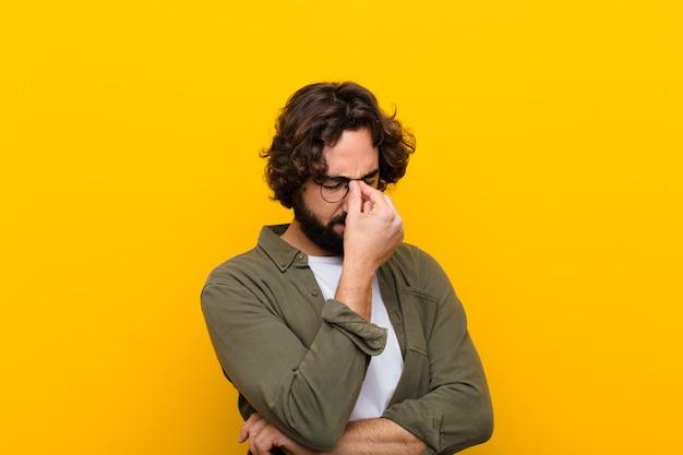 Młody szalony człowiek czuje się zestresowany, nieszczęśliwy i sfrustrowany, dotyka czoła i cierpi na migrenę silnego bólu głowy żółta ściana