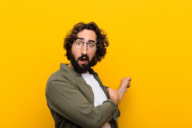 Młody szalony człowiek czuje się zszokowany i zaskoczony, wskazując na copyspace z boku ze zdumionym, otwartym ustami na żółtej ścianie