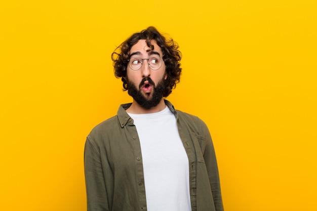 Młody szalony człowiek czuje się zszokowany, szczęśliwy, zaskoczony i zaskoczony, patrząc w bok z otwartymi ustami na żółtej ścianie