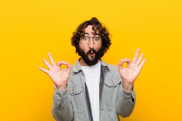 Młody szalony człowiek czuje się zszokowany, zdziwiony i zaskoczony, pokazując aprobatę czyniąc dobrze znakiem obiema rękami żółtą ścianą