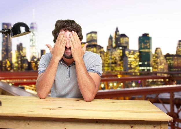 Młody szalony człowiek na stole zaskoczony wypowiedzi