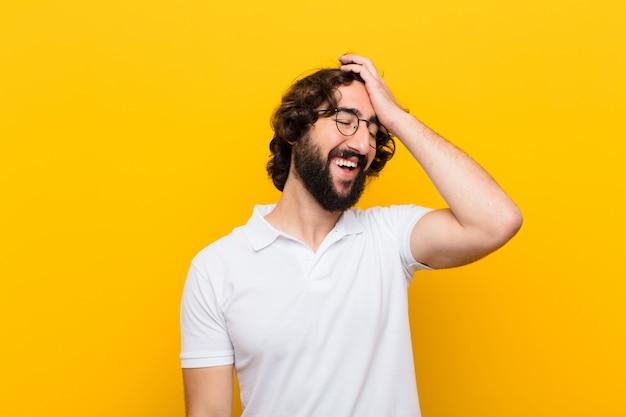 """Młody szalony człowiek śmieje się i klepie się w czoło, jak powiedzenie: """"och!""""! zapomniałem lub to był głupi błąd na żółtej ścianie"""