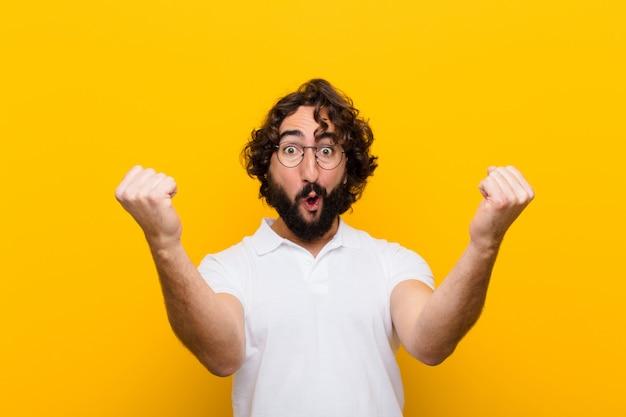 Młody szalony człowiek świętuje niewiarygodny sukces jak zwycięzca, wyglądający na podekscytowanego i radosnego mówiąc: weź to! na żółtej ścianie