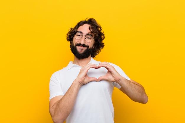 Młody szalony człowiek uśmiecha się i czuje się szczęśliwy, słodki, romantyczny i zakochany, dzięki czemu obiema rękami na żółtej ścianie robi kształt serca