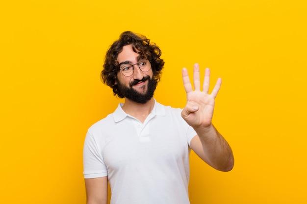 Młody szalony człowiek uśmiecha się i szuka przyjazny pokazując numer cztery lub czwarty ręką do przodu odliczanie