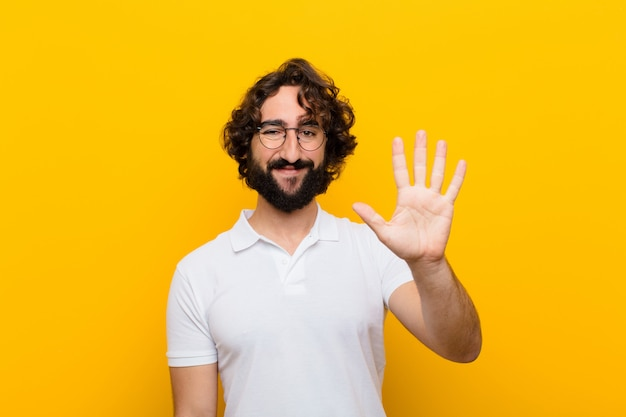 Młody szalony człowiek uśmiecha się i wygląda przyjaźnie, pokazuje numer pięć lub piąty ręką do przodu, odliczając do żółtej ściany