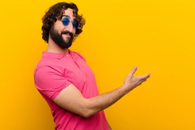 Młody szalony człowiek uśmiecha się, wita cię i oferuje drżenie ręki, aby zamknąć udaną transakcję, koncepcja współpracy przeciwko ścianie pomarańczowy