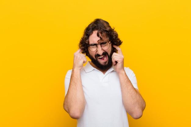 Młody szalony człowiek wyglądający na wściekłego, zestresowanego i zirytowanego, zasłaniający uszy ogłuszającym hałasem, głośną muzyką żółta ściana