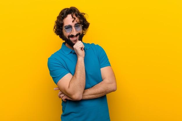 Młody szalony człowiek wyglądający szczęśliwy i uśmiechnięty z ręką na brodzie, zastanawiając się, zadając pytanie, porównując opcje pomarańczowe ściany