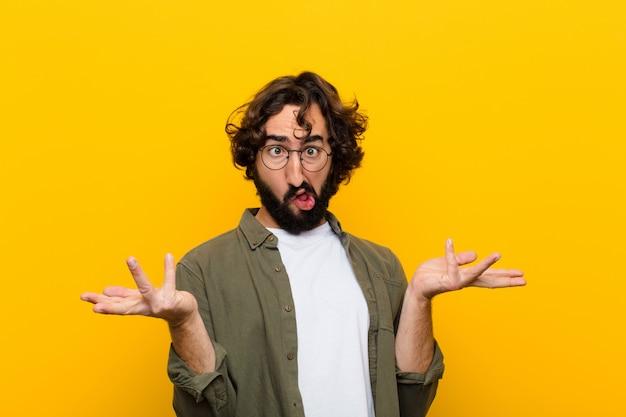 Młody szalony człowiek wzrusza ramionami z głupim, szalonym, zdezorientowanym, zdziwionym wyrazem twarzy, czuje się zirytowany i nieświadomy żółtej ściany