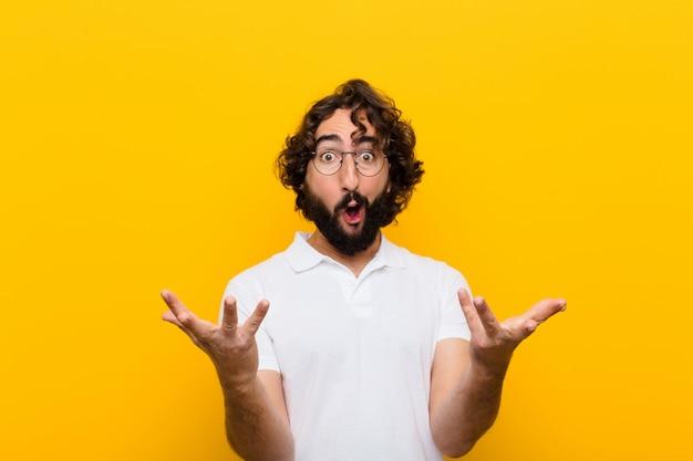 Młody szalony człowiek z otwartymi ustami i zdumiony, zszokowany i zaskoczony niewiarygodną żółtą ścianą niespodzianki