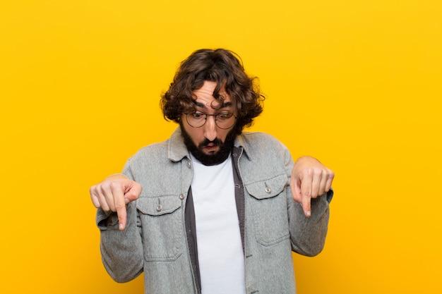 Młody szalony człowiek z otwartymi ustami obiema rękami skierowanymi w dół, wyglądający na zszokowaną, zdziwioną i zaskoczoną żółtą ścianę