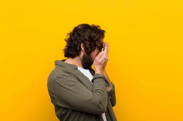 Młody szalony człowiek zakrywający oczy rękami o smutnym, sfrustrowanym wyrazie rozpaczy, płacz, żółta ściana z boku