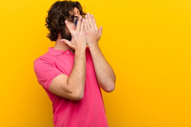 Młody szalony człowiek zakrywający twarz rękami, zerkający między palcami ze zdziwionym wyrazem twarzy i patrząc na boczną pomarańczową ścianę