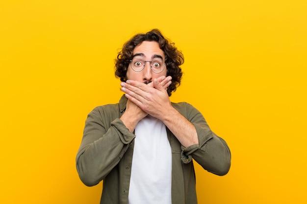 Młody szalony człowiek zakrywający usta dłońmi z zszokowanym, zaskoczonym wyrazem twarzy, trzymający w tajemnicy lub mówiąc: ups