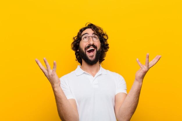 Młody szalony czuje się szczęśliwy, zaskoczony, szczęśliwy i zaskoczony, świętując zwycięstwo obiema rękami w powietrzu