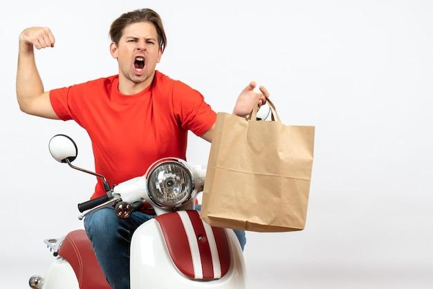 Młody szalony emocjonalny kurier facet w czerwonym mundurze siedzi na skuterze trzymając papierową torbę pokazując jego muskularny na białej ścianie