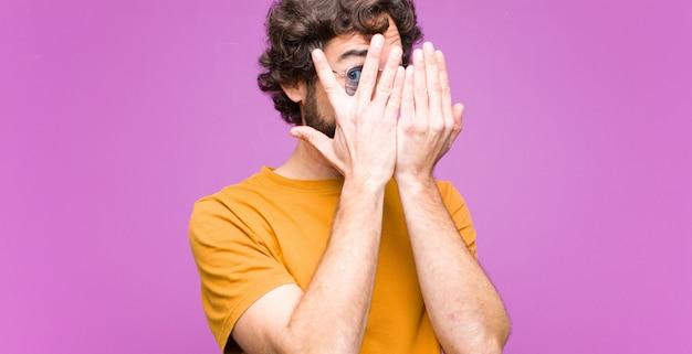 Młody szalony fajny człowiek czuje się przestraszony lub zawstydzony, zerkając lub szpiegując oczy na wpół zasłonięte rękami na płaskiej ścianie
