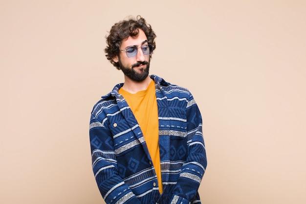 Młody szalony fajny człowiek czuje się smutny, zdenerwowany lub zły i patrzy w bok z negatywnym nastawieniem, marszcząc brwi w sporze o płaską ścianę
