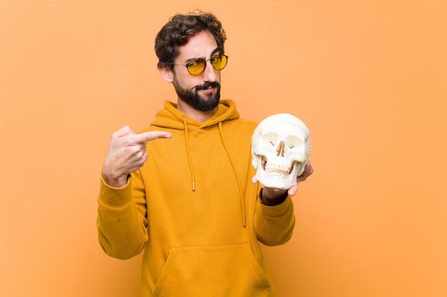 Młody szalony fajny człowiek trzyma model ludzkiej czaszki na ścianie pomarańczowy