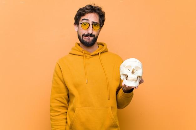Młody szalony fajny człowiek trzyma model ludzkiej czaszki przed pomarańczową ścianą