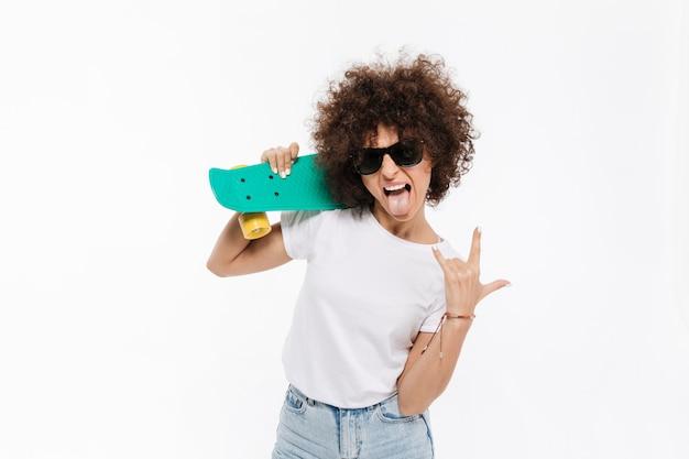 Młody szalony kobieta pokazuje rockowego gest podczas gdy stojący