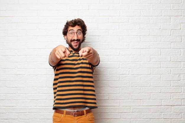 Młody szalony lub niemądry mężczyzna gestykuluje emocje przeciw ściana z cegieł tłu i wyraża