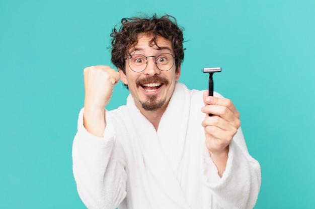 Młody szalony mężczyzna goli brodę brzytwą