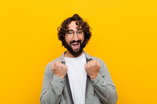 Młody szalony mężczyzna krzyczy triumfalnie, śmiejąc się i czując się szczęśliwy i podekscytowany, świętując sukces żółtą ścianę