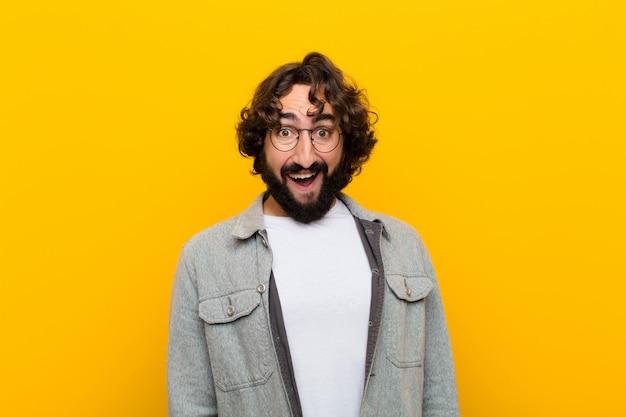 Młody szalony mężczyzna wyglądający na szczęśliwego i mile zaskoczonego, podekscytowany zafascynowaną i zszokowaną miną żółtą ścianą