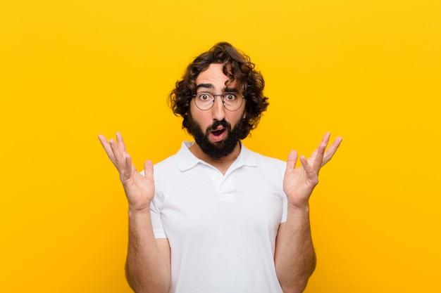 Młody szalony mężczyzna wyglądający na zszokowanego i zaskoczonego, ze szczęką opadającą ze zdziwienia na widok czegoś niewiarygodnego na żółtej ścianie