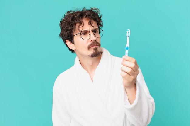 Młody szalony mężczyzna ze szczoteczką do zębów