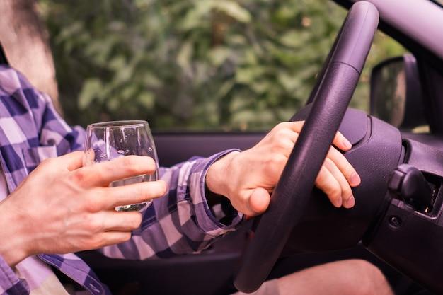 Młody szalony pijany mężczyzna prowadzący samochód i pijący alkohol