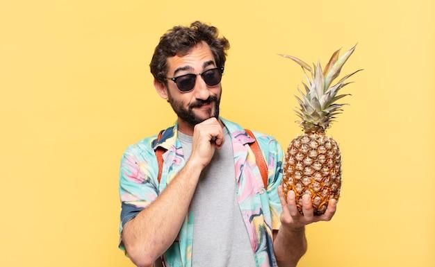 Młody szalony podróżnik człowiek myśli wyrażenie i trzyma ananas