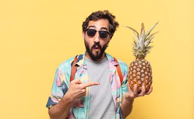 Młody szalony podróżnik przestraszony wyrazem twarzy i trzymając ananas