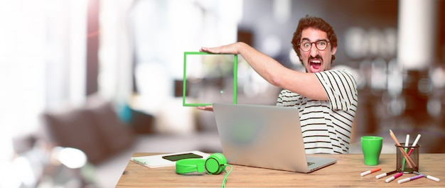 Młody szalony projektant grafik komputerowych na biurku z laptopem