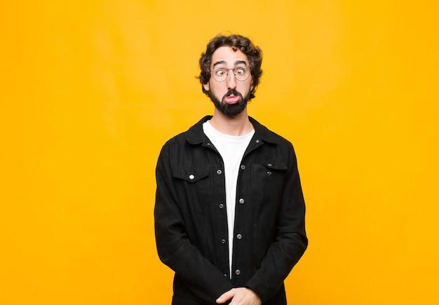 Młody szalony przystojny mężczyzna wyglądający na głupkowatego i zabawnego z głupim zezem, żartujący i wygłupiający się na pomarańczowej ścianie