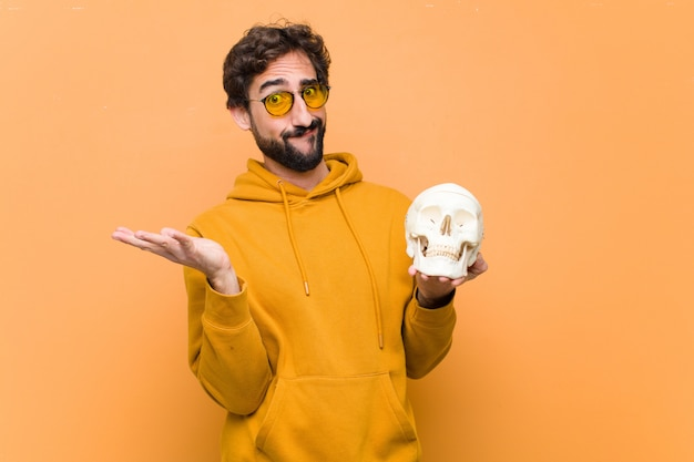 Młody szalony super trzyma model ludzkiej czaszki na pomarańczowej ścianie