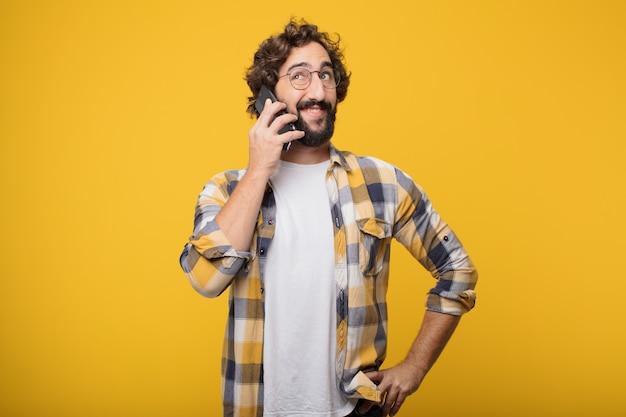 Młody szalony szalony człowiek pozie z inteligentny telefon komórkowy