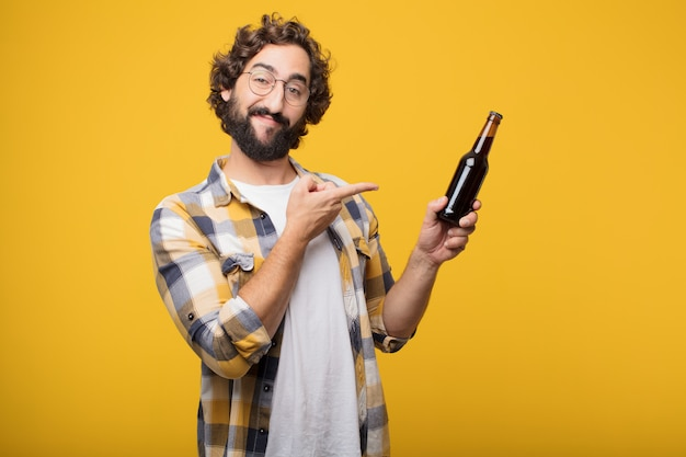 Młody szalony szalony człowiek pozować z butelką piwa.