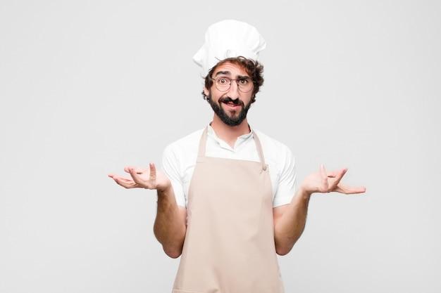 Młody szalony szef kuchni czuje się nieświadomy i zdezorientowany, nie jestem pewien, który wybór lub opcję wybrać, zastanawiając się przy białej ścianie