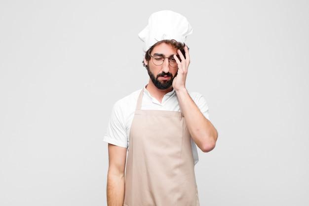 Młody szalony szef kuchni czuje się znudzony, sfrustrowany i senny po męczącym, nudnym i żmudnym zadaniu, trzymając twarz ręką nad białą ścianą