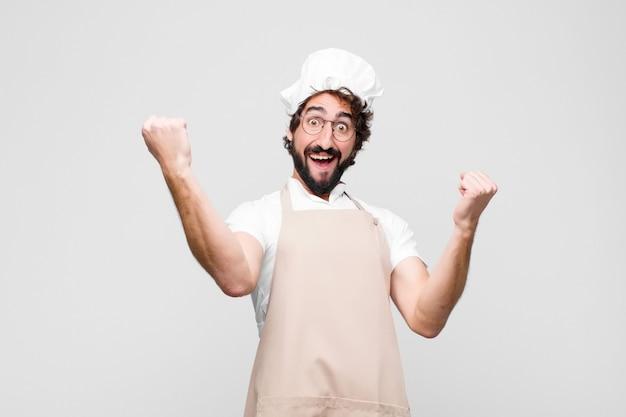 Młody szalony szef kuchni krzyczy triumfalnie, wyglądając jak podekscytowany, szczęśliwy i zaskoczony zwycięzca, świętujący nad białą ścianą