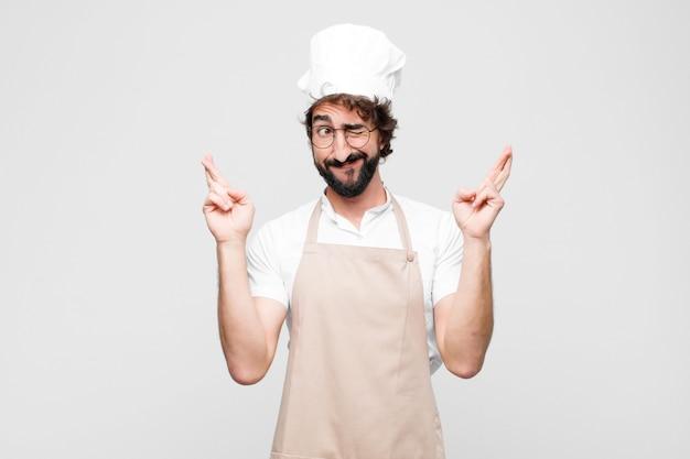 Młody szalony szef kuchni uśmiecha się i niespokojnie krzyżuje oba palce, czuje się zaniepokojony i pragnąc powodzenia na białej ścianie