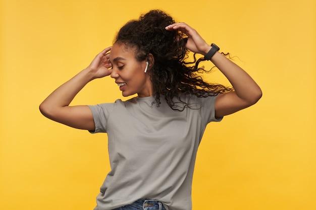 Młody szczęśliwy afroamerykanin nosi szary t-shirt, tańcząc, słuchając dobrej muzyki przez słuchawki
