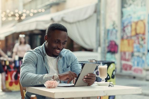 Młody szczęśliwy afroamerykanin używa komputera typu tablet siedzi na ulicy kawiarni z graffiti na tle.