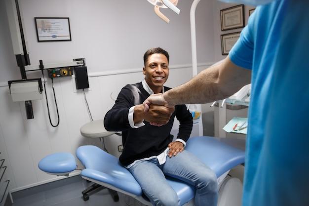 Młody szczęśliwy afroamerykański mężczyzna drżenie ręki dentysta ma wizytę w klinice medycznej.